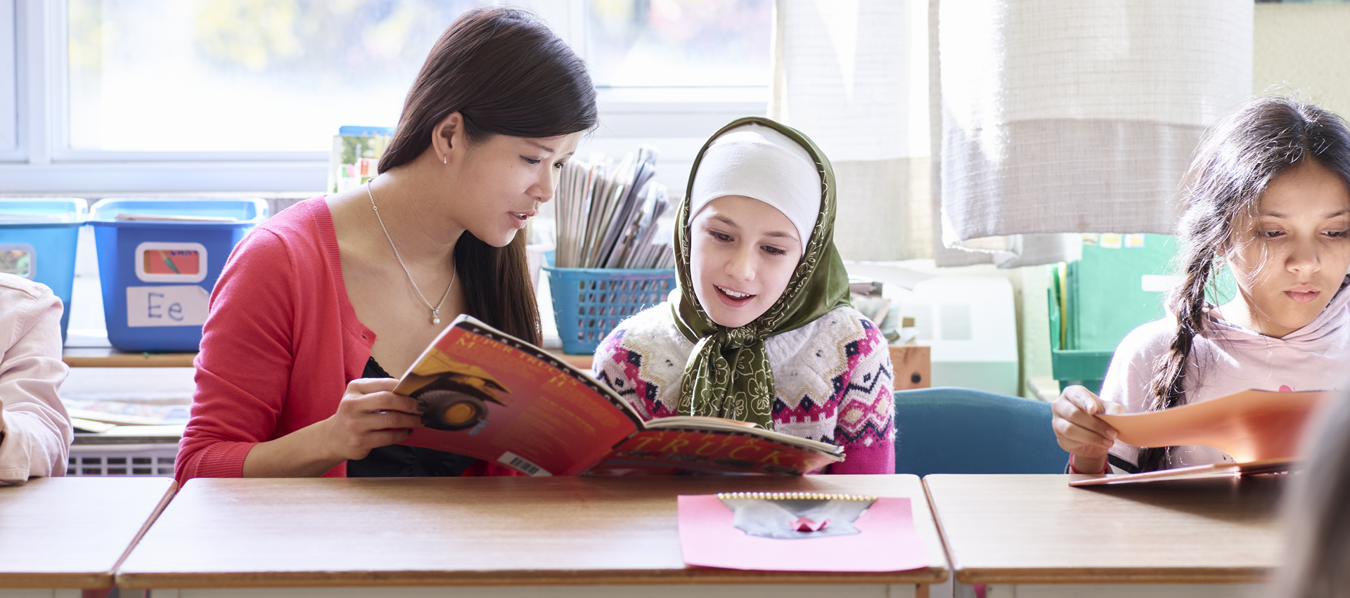 A teacher reads to a student